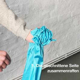 Eine Hand hält das zusammengeraffte Flying Pilates Tuch.