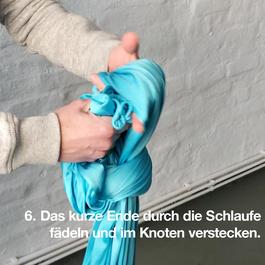 Das kurze Ende des Tuches wird durch die geknotete Schlaufe gelegt.
