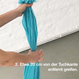 Das geraffte Tuch wird mit beiden Händen gehalten.