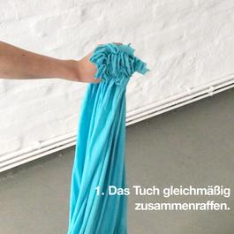 Das zusammengeraffte Tuch wird in der Hand gehalten.
