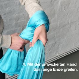 Eine Hand hält das kurze Ende, die zweite Hand greift nach dem langen Ende des Tuches