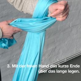 Das äußere Ende des Tuches wird mit einer Hand über das lange Ende gelegt.