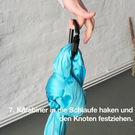 Ein Karabiner wird in den Tuchknoten gehakt und von einer Hand gehalten.
