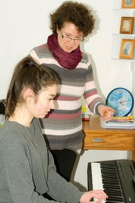 Foto: Frau Pevzner gibt einer spielenden fortgeschrittenen Schülerin mit dem Finger den Takt