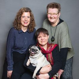 Das Foto zeigt Ilka Haederle, Doris Bewernitz, eine Mopshündin und mich. Wir lächeln in die Kamara und sind verdammt schick gemacht.