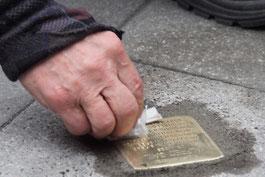 eine Hand ist zu sehen, die mit einem kleinen Lappen auf dem Stein wischt