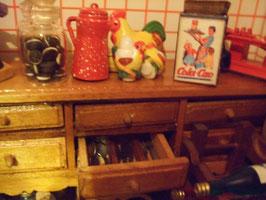 La lata de Cola Cao es de Rosa CM y el tarro de galletas (oreo) lo compró mi hermana en París. Dentro del cajón está la cubertería.