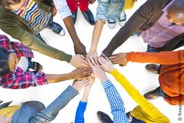 Ansicht von oben: Menschen unteerschiedlicher Hautfarbe stehen im Kreis und halten in der Mitte ihre Hände aufeinander