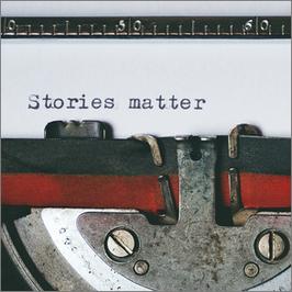 """Das Farbband, rot-schwarz, einer alten Schreibmaschinen mit dem Text auf dem eingespannten Papier """"Stories matter""""."""