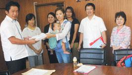 児童館の早期建設を求める署名を中山市長に手渡す八尋代表ら=30日午前、市役所