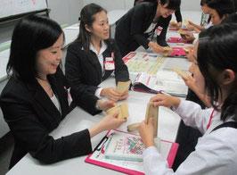 拠点での職場体験学習風景。札勘体験の講義で、生徒に札勘の方法を教える職員。