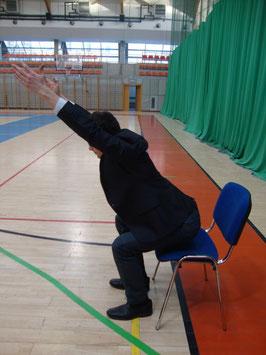 Rehabilitacja kręgosłupa: przysiady z wyciągniętymi ramionami.