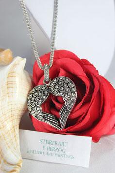 Geflügeltes Herz mit Strasssteinen besetzt und langer Kette.