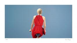 Liebchen - o.T., Fahrradfahrerin in rotem Kleid, blau
