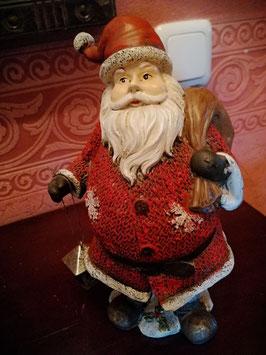 nostalgischer Weihnachtsmann mit rotem Strickmantel, Sack über der Schulter und kleine Metalllaterne in der Hand