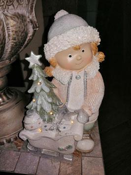 Wintermädchen mit Schlitten und Tanne, die Tanne ist mit LED-Licht ausgestattet