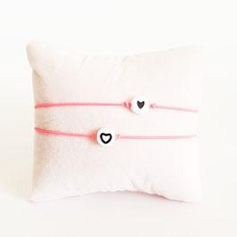 Vriendschapsbandjes 2x Fluor roze elastiek + Witte kraal met zwart hartje