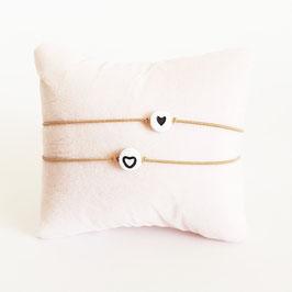 Vriendschapsbandjes 2x Beige elastiek + Witte kraal met zwart hartje