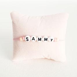 Roze elastiek + Witte kraal met zwarte letter + licht roze en beige rocaille
