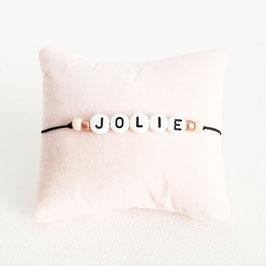 Zwart elastiek + Witte kraal met zwarte letter + licht roze en rosé gouden rocaille