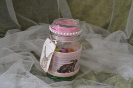 Dekoglas mit Banderole und rosa Federn im Deckel