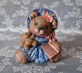 Bärenmutter mit blauem Kleid und rosa Buch