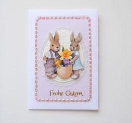 Osterkuvert weiß-flieder mit Schmucksteinen. Zwei Hasen mit Ei.
