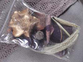 1 Beutel mit lila gefärbten Hölzern, Kugeln, Naturmaterialien und goldfarbener Blüte