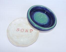 """Weiße Seifenschale mit roter Schrift """"SOAP""""  (li.im Bild), die blaue Schale ist verkauft."""