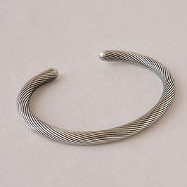 Bracelet N° 59. Jonc tout rond , simple. La patine en fait discrètement ressortir les fines stries. Bronze recouvert d'argent pur.