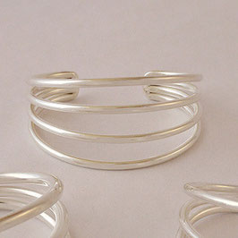 Bracelet N°22. Sobre et élégant, quatre fils en toute simplicité (diamètre du fil: 3 mm). Bronze recouvert d'argent pur. Parure possible avec le collier à trois fils de même facture.