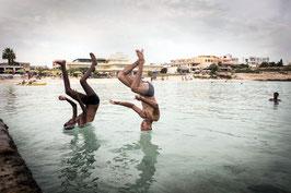 IB 49 -  Lampedusa: due profughi sopravvissuti al naufragio del 3 ottobre, si svagano in spiaggia, 2013