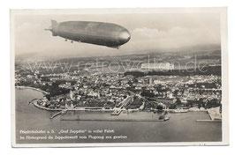 """Alte Postkarte FRIEDRICHSHAFEN - Luftschiff """"Graf Zeppelin"""" in voller Fahrt. Im Hintergrund die Zeppelinwerft vom Flugzeug aus gesehen - 1931"""