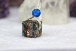 Großer Würfel mit zwei unterschiedlichen Kristallschichten außen und einem Metallkern aus Zink, Kupfer und blauem Stahl