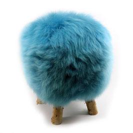 Tabouret scandinave fabriqué avec 4 pieds en bois de bouleau naturel brut et son assise en peau de mouton teintée bleu turquoise
