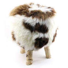 Tabouret scandinave fabriqué avec 4 pieds en bois de bouleau naturel brut et son assise en peau de mouton marron et blanc tachetée