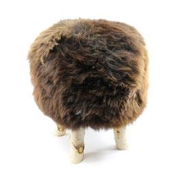 Tabouret scandinave fabriqué avec 4 pieds en bois de bouleau naturel brut et son assise en peau de mouton marron naturelle