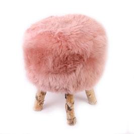 Tabouret scandinave fabriqué avec 4 pieds en bois de bouleau naturel brut et son assise en peau de mouton teintée rose poudré