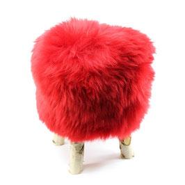 Tabouret scandinave fabriqué avec 4 pieds en bois de bouleau naturel brut et son assise en peau de mouton teintée rouge ferrari