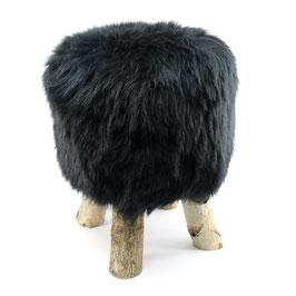 Tabouret scandinave fabriqué avec 4 pieds en bois de bouleau naturel brut et son assise en peau de mouton teintée noire
