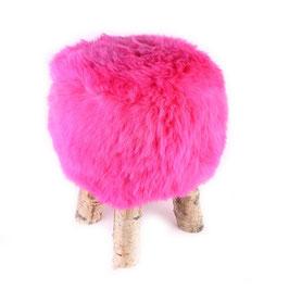 Tabouret scandinave fabriqué avec 4 pieds en bois de bouleau naturel brut et son assise en peau de mouton teintée rose fushia