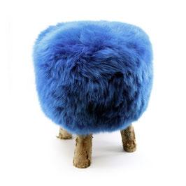 Tabouret scandinave fabriqué avec 4 pieds en bois de bouleau naturel brut et son assise en peau de mouton teintée bleu dur