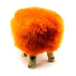 Tabouret scandinave fabriqué avec 4 pieds en bois de bouleau naturel brut et son assise en peau de mouton teintée orange vintage