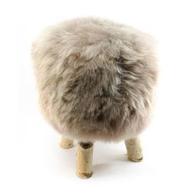 Tabouret scandinave fabriqué avec 4 pieds en bois de bouleau naturel brut et son assise en peau de mouton teintée grège