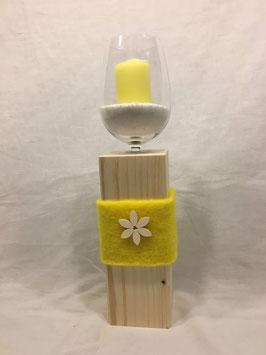 Weinglas auf Holzsäule mit Blume gelb