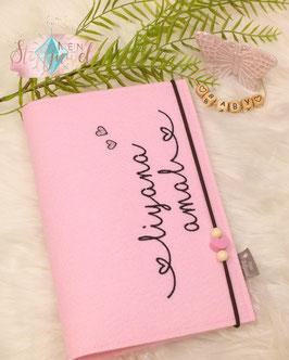 U-hefthülle rosafarbener Filz Bsp. liyana amal mit Glitzerherzchen und schwarzer Schrift, 1 rosa Holzherzperle und 2 runde creme