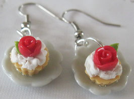 Cupcakes-Ohrringe mit roter Rose auf weißem Teller