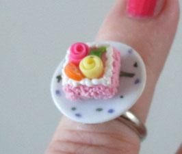 Rosa viereckiger Torten-Ring auf Teller