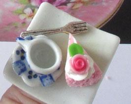 Ring mit Tasse, Torte und Kuchengabel auf 4-eckigem Teller