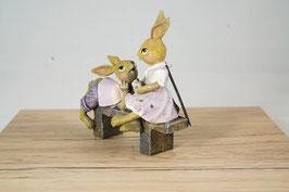 Kaninchenpaar auf Bank flieder
